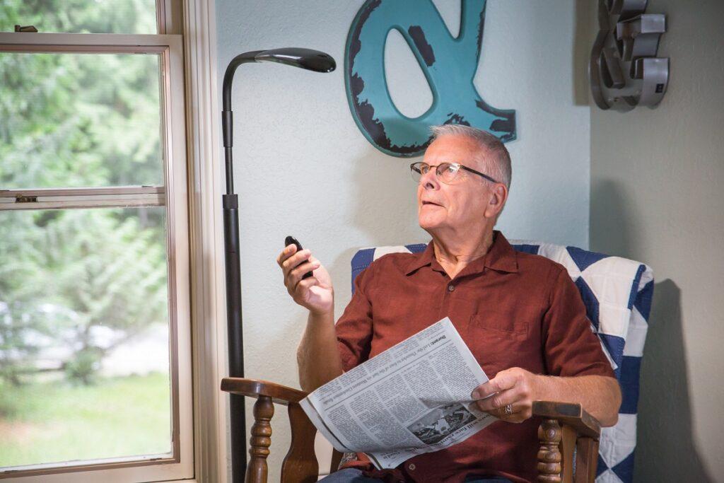 Man reading newspaper using Stella light.